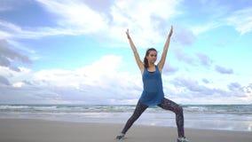 A jovem mulher pratica a ioga em uma praia no nascer do sol na frente do mar Manhã ginástica Mãos da elevação filme