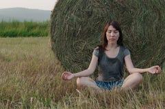 A jovem mulher pratica a meditação no pacote de feno do fundo imagens de stock royalty free