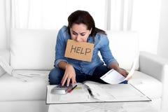 A jovem mulher preocupou-se em casa em explicar do esforço desesperado em problemas financeiros fotografia de stock