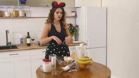 A jovem mulher prepara ingredientes de mistura da massa o na bacia usando o batedor de ovos na cozinha Alimento caseiro Tiro Slow video estoque