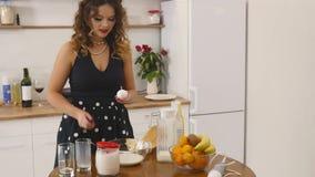 A jovem mulher prepara ingredientes de mistura da massa o na bacia usando o batedor de ovos na cozinha Alimento caseiro Tiro Slow filme