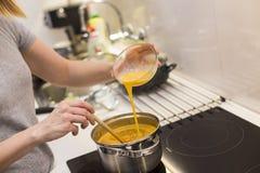 A jovem mulher prepara o alimento em uma cozinha moderna Fotografia de Stock Royalty Free