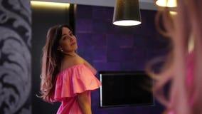 A jovem mulher prepara-se na frente de um espelho, olhando si mesma feliz video estoque