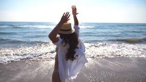 A jovem mulher puxa seu noivo na costa de mar e em apreciar férias ou feriado de verão Menina no chapéu que guarda a mão masculin filme