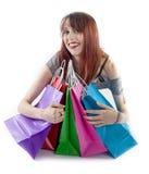 Jovem mulher que abraça sacos de compras coloridos Fotografia de Stock