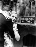 Jovem mulher que abraça um homem e que aponta para uma placa da informação (todas as pessoas descritas não são um vivo mais longo Imagem de Stock