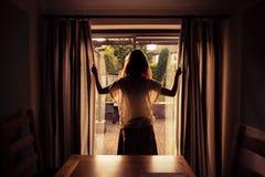 Jovem mulher que abre as cortinas no nascer do sol Imagens de Stock Royalty Free