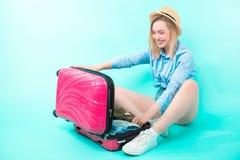 Jovem mulher que abre sua mala de viagem após feriados imagem de stock royalty free