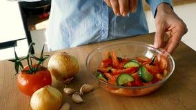 Jovem mulher que adiciona o sal na salada com os vegetais na bacia de vidro, v?deo de movimento lento vídeos de arquivo