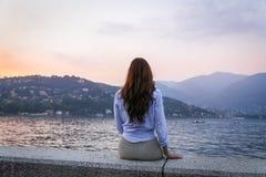 Jovem mulher que admira o por do sol no lago Como Fotos de Stock