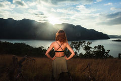 Jovem mulher que admira o por do sol sobre a baía Fotos de Stock Royalty Free