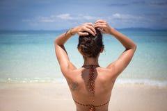 Jovem mulher que admira a opinião do mar Foto de Stock