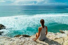 Jovem mulher que admira a paisagem bonita dos penhascos e do oceano em Portugal imagem de stock
