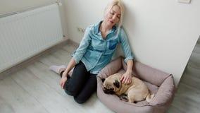 Jovem mulher que afaga seu cão que senta-se no assoalho filme