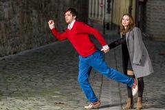 Jovem mulher que agarra seu noivo pelo bolso traseiro de suas calças de brim Imagens de Stock Royalty Free