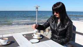 Jovem mulher que agita o café com uma colher de chá em um leite de derramamento da mulher exterior do cafeyoung no café em um caf filme