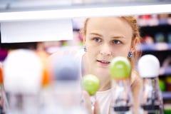 Jovem mulher que analisa produtos em uma loja Fotografia de Stock