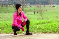 Jovem mulher que analisa a trilha antes de correr em um dia de inverno frio na trilha do treinamento de um parque urbano fotos de stock