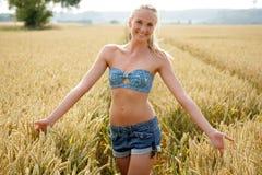 Jovem mulher que anda através de um campo de milho Fotos de Stock