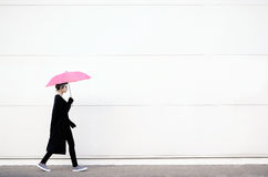 Jovem mulher que anda com guarda-chuva cor-de-rosa imagem de stock