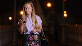 Jovem mulher que anda com smartphone e sorriso filme