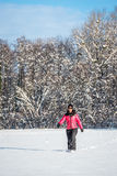 Jovem mulher que anda em um campo coberto de neve Foto de Stock