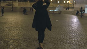 Jovem mulher que anda na cidade da noite apenas Fêmea atrativa que espera alguém no centro de cidade, no quadrado filme