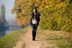 Jovem mulher que anda na floresta do outono fotografia de stock royalty free