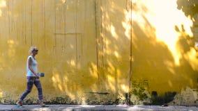 Jovem mulher que anda na frente da parede amarela em Vietname filme