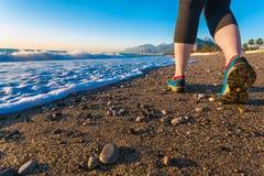 Jovem mulher que anda na praia da areia ao longo da ressaca do mar em sapatas da manhã perto acima Fotos de Stock