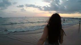 Jovem mulher que anda na praia que guarda a mão do homem no ponto da câmera da ação do por do sol de Vew da menina de sorriso fel vídeos de arquivo