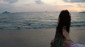 Jovem mulher que anda na praia que guarda a mão do homem no ponto da câmera da ação do por do sol de Vew da menina de sorriso fel filme