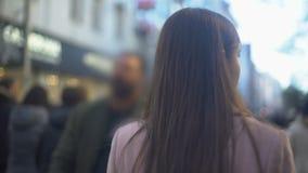 Jovem mulher que anda na rua de compra aglomerada, destino turístico, vista traseira filme