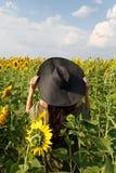 Jovem mulher que anda no campo com girass?is Mo?a bonita que aprecia a natureza no campo dos girass?is no por do sol fotos de stock