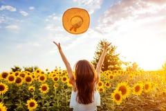 Jovem mulher que anda no chapéu de jogo de florescência do campo do girassol acima e que tem o divertimento F?rias de ver?o imagens de stock