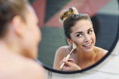 Jovem mulher que aplica a composição com a escova no banheiro imagem de stock royalty free