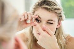 Jovem mulher que aplica a lente de contato fotografia de stock