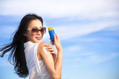 Jovem mulher que aplica a loção da proteção do sol Fotografia de Stock