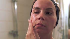Jovem mulher que aplica o creme cosmético na cara no banheiro vídeos de arquivo
