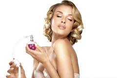 Jovem mulher que aplica o perfume em seu espaço do pescoço para o texto Imagem de Stock