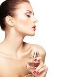 A jovem mulher que aplica o perfume nsi mesma isolou-se no backgr branco Imagens de Stock