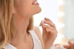 Jovem mulher que aplica o perfume perto do espelho dentro imagem de stock royalty free