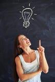 Jovem mulher que aponta acima com seu dedo no desenho de giz do ligh Fotos de Stock Royalty Free