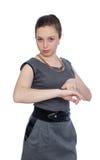 Jovem mulher que aponta em seu relógio Fotografia de Stock Royalty Free