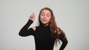 Jovem mulher que aponta o dedo acima e que tem uma ideia isolada em um fundo branco filme