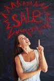 Jovem mulher que aponta o dedo acima na inscrição vermelha da venda do giz sobre Imagem de Stock