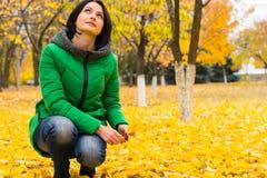 Jovem mulher que aprecia as folhas de outono amarelas brilhantes Fotos de Stock Royalty Free