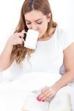 Jovem mulher que aprecia a leitura e beber do café na cama imagens de stock royalty free