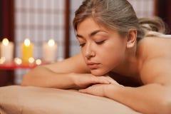 Jovem mulher que aprecia a massagem profissional imagem de stock