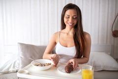Jovem mulher que aprecia o café da manhã na cama foto de stock